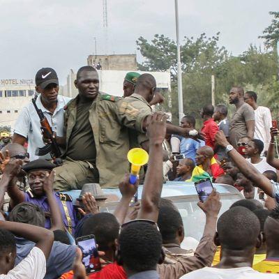 Maliska soldater sitter på en pickupbil och omringas av människor som står på gatan.