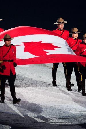 9 Kanadan kuninkaallista ratsupoliisia kantaa välissään Kanadan lippua