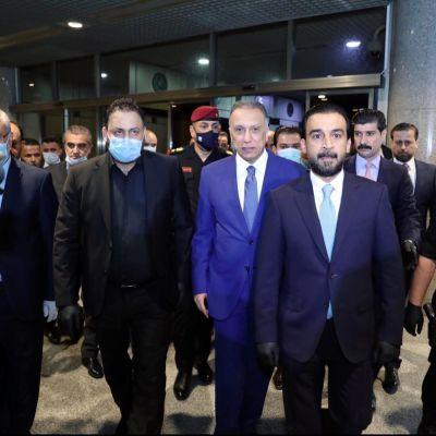 Iraks nya premiärminister Mustafa Kadhemi (i blått i mitten) anländer till förtroendeomröstningen i parlamentet.