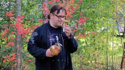 Jyrki Kasvi syksyisessä metsässä sieniretkellä, nuuhkii herkkutattia. Lehdissä ruskan punaisia värejä.