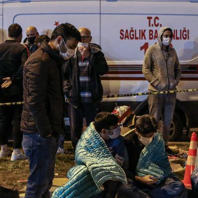 Människor sitter på en trottoar. De bär munskydd och en del är insvepta i filtar. I bakgrunden en ambulans.