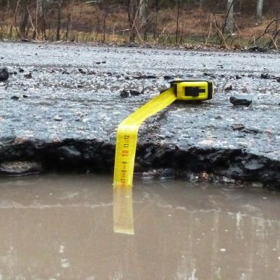 En vattenfylld grop i asfalten med ett måttband nerstucket. Måttbandet visar på lite under sju centiometer vatten.