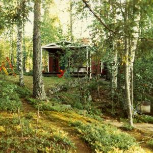 Tyypillinen suomalainen kesämökkimaisema, jossa sekametsän keskellä seisoo kesämökki keinuineen.