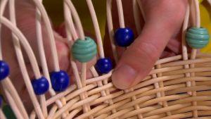 Avsluta flätningen med pärlor och böjda kanter.