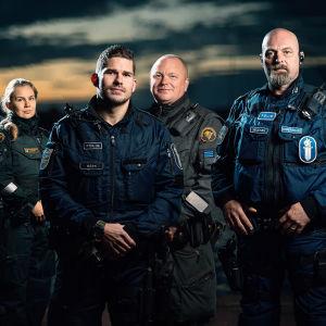 Sju poliser och sjöbevakare står utomhus. Bakgrunden är en somrig natthimmel.