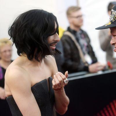 Euroviisuvoittaja Conchita Wurst ja Pertti Kurikan Nimipäivät -yhtyeen Kari Aalto juttelevat Euroviisujen avajaisseremoniassa Wienissä 17. toukokuuta.