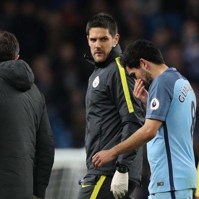 Polvensa loukannut Ilkay Gündogan poistuu kentältä huoltajien saattamana Valioliigan ottelussa Manchester City - Watford.