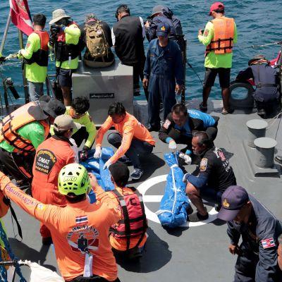 Pelastustyöntekijöitä laivalla.