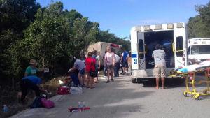 Sjukvårdspersonal hjälper skadade och chockade turister vid en vägren efter en bussolycka. Olycksbussen i bakgrunden har vält och ligger på sida vid sidan om vägen.