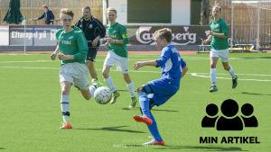 Ekenäs IF:s fotbollspojkar i vita shorts och gröna tröjor spelar fotboll.