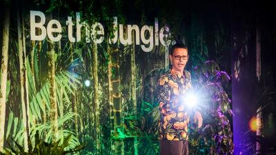 Olof står framför en fond av gröna djungelväxter.