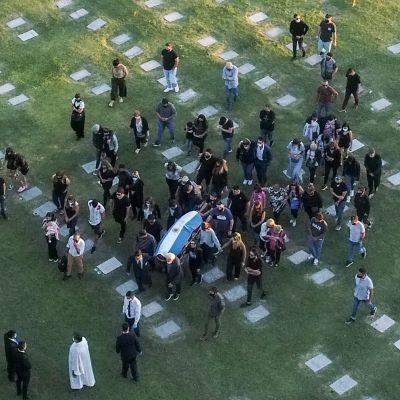 Flygbild från kyrkogård med kista och omgivande människor.