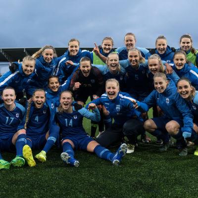 Suomen naisten jalkapallomaajoukkue nurmella iloiset ilmeet kasvoillaan.