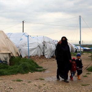 Mamma med barn framför läger i Syrien.