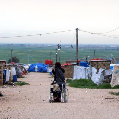 Mustaan kaapuun pukeutunut nainien työntää lasta pyörätuolissa. Ympärillä on telttoja ja pieniä tiilirakennuksia.