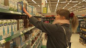 ung kvinna letar i mjölkhyllan