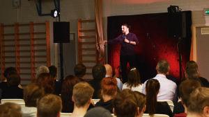 En man står på scen och talar i en mikrofon. Han viftar med ena handen medan han talar. Framför scenen sitter många ungdomar.