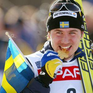 Svenske ex-längdåkarstjärnan Per Elofsson biter på en guldmedalj.