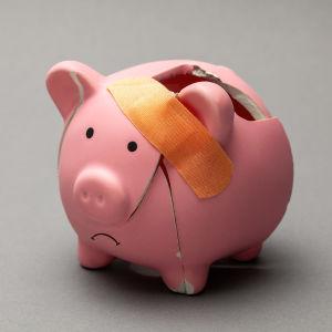rikkinäinen säästöpossu on paikattu laastarilla ja suupielet on alaspäin
