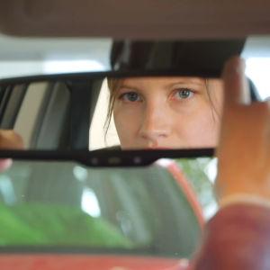 Eläinlääkärikandi Veera Haukijärvi katsoo auton peruutuspeilistä