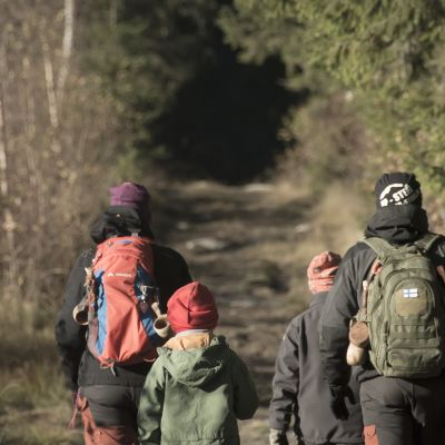 Isä ja äiti kahden poikansa kanssa päiväretkellä Perhonjoen retkeilureitillä.