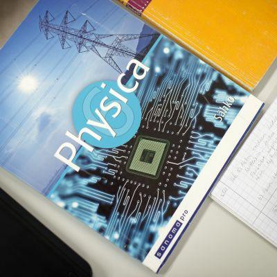 Lukiolaisen fysiikan kirja pulpetilla.
