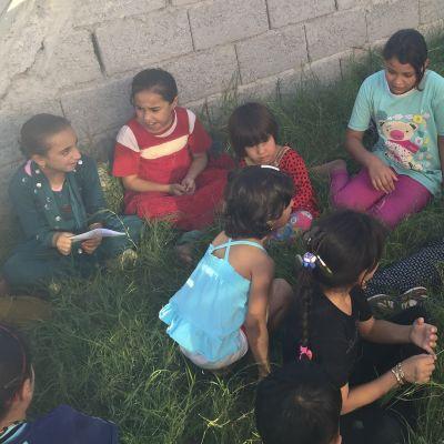 nainen istuu nurmikolla lasten kanssa