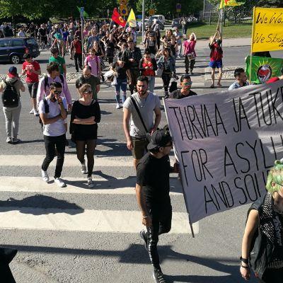 Mielenosoittajat ylittämässä katua banderollien kanssa