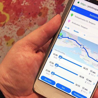 Kädessä kännykkä, jossa auki uusi Repa Reittiopas -sivusto