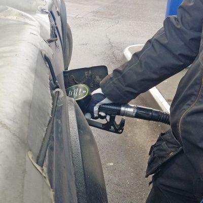 Mies tankkaa autoonsa Dieseliä.
