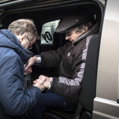 Vanhaa miestä autetaan ulos monipalveluautosta Kannuksessa.
