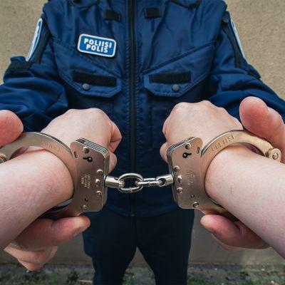 Poliisi laittaa käsiraudat