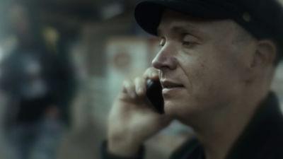 Den blinda och rulllstolsbundna Jaakko talar i mobil med en oskarp figur i bakgrunden.