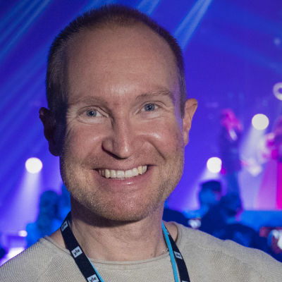 Sångcoachen Tomas Höglund poserar framför MGP-scenen.