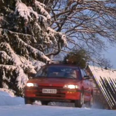 Auto ajaa lumisellä tiellä