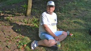 En man i vit t-skjorta sitter på en gräsmatta. Han håller i en vattenflaska och tittar in i kameran.