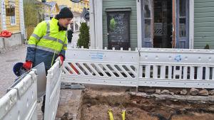 En man i gul jacka lutar sig över ett staket och tittar ner i en grop. Han står i gamla stan i Borgå.