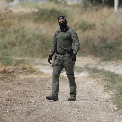 En person från de israeliska specialsäkerhetsstyrkorna letar efter fångarna som rymt på ett stort fält.