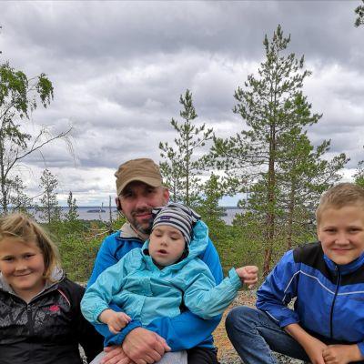 Ossi, isi-Jussi, Eetu ja Väinö Lampinen retkellä. Järvi siintää taustalla.