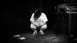 Mustavalkoisessa kuvassa mies on kyykistyneenä lavalla mikki kädessään, lippis peittää kasvot. Päällä valkoinen Love records -paita