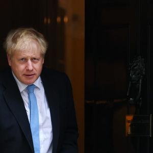 Premiärminister Boris Johnson i kostym och blå slips. Till höger en dörr.