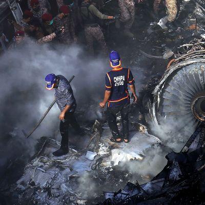 Pelastustyöntekijät etsivät eloonjääneitä lentokoneen ja tuhoutuneiden rakennusten raunioista.
