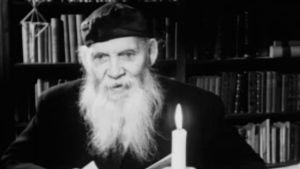 Kirjailija Frans Emil Sillanpää lukee joulupakinaansa lapsille kynttilänvalossa