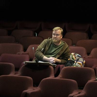 Teatteriohjaaja Matti Tolvanen seuraa harjoituksia katsomosta.