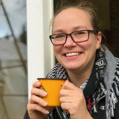 Nainen istuu kuistin oviaukossa ja juo kahvia keltaisesta mukista.