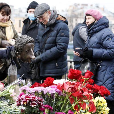 Ihmiset tuovat kukkia enkelipatsaalle joka on omistettu koronaan kuolleille terveydenhoitohenkilöstölle.