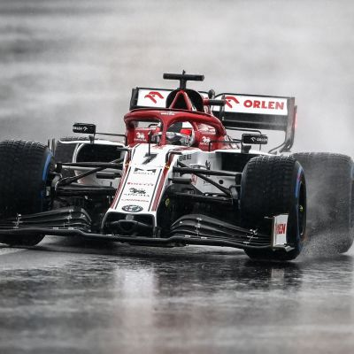 Kimi Räikkönen kör i regn i en kurva.