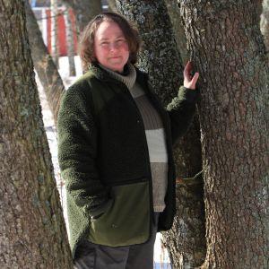 Nainen seisoo kevättalvella auringonpaisteessa puiden välissä.