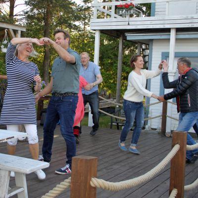 Joukko ihmisiä tanssii merenrannassa pienellä terassilla.