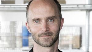 en man i svart kavaj och vit skjorta